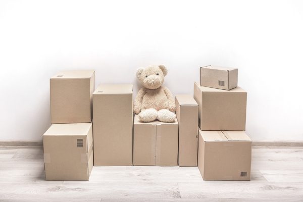 Empty room with a white wall and cardboard boxes with unbranded barcode and teddy bear on the floor.