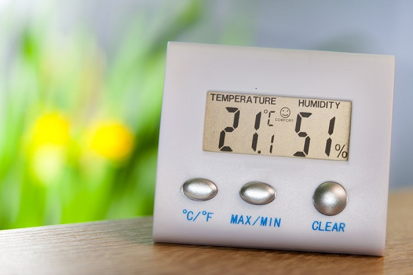 Hygrometer on a table shows comfort temperature and humidity
